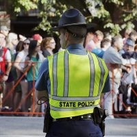 A Massachusetts State Police officer keeps watch over a line of people waiting to pass through security before rehearsal for the annual Boston Pops Fireworks Spectacular on the Esplanade in Boston in 2016. (Michael Dwyer/AP)