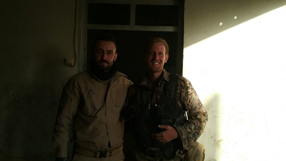 Caleb Stevens (right) in Raqqa with Mehmed, a Kurdish friend who was also fighting there. The picture was taken just after the ISIS forces in the city surrendered. (Courtesy Caleb Stevens)
