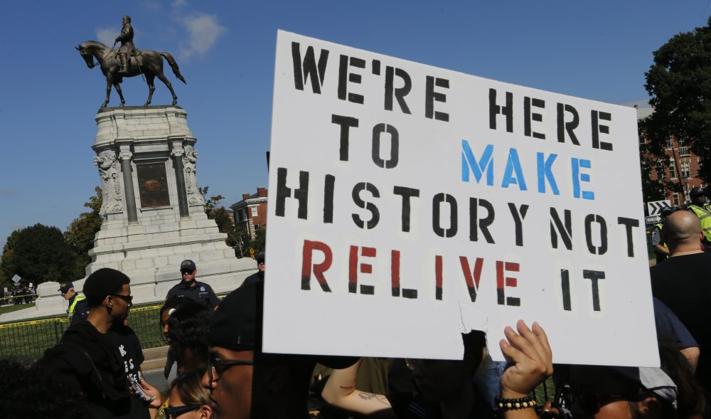 Protesters hold signs in front of the statue of Confederate General Robert E. Lee on Monument Avenue in Richmond, Va., Saturday, Sept. 16, 2017. (Steve Helber/AP)