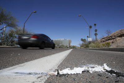 A vehicle goes by the scene of Sunday's fatality where a pedestrian was stuck by an Uber vehicle in autonomous mode, in Tempe, Ariz., Monday, March 19, 2018. (Chris Carlson/AP)