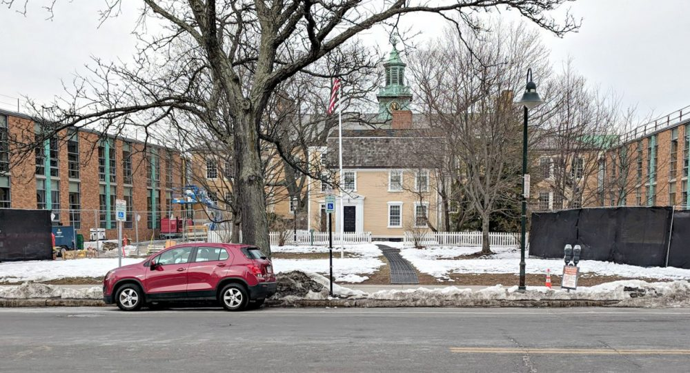 The renaming of a school in Brookline brings up a bigger question, writes Jessica Ullian. Why are certain figures remembered while others are pushed aside?  In this photo: The small yellow structure is the original home of Edward Devotion, circa 1740. The darker yellow structure is the original elementary school. The red-brick structure is the new construction. (Courtesy)