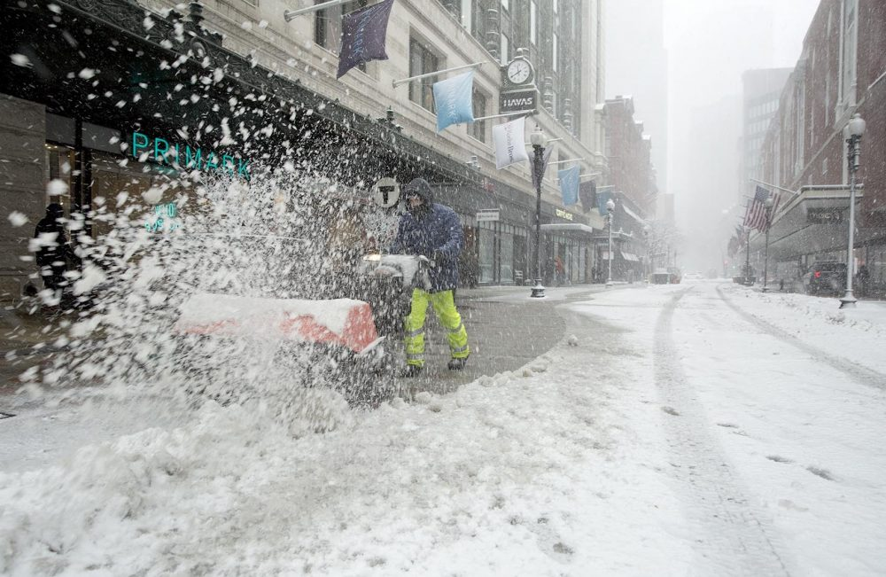 A power brush clears sidewalks on Summer Street in downtown Boston. (Robin Lubbock/WBUR)