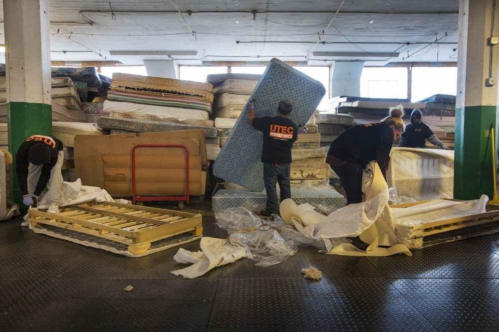 Workers at the UTEC Mattress Warehouse tackle piles of mattresses to breakdown for landfills. (Jesse Costa/WBUR)