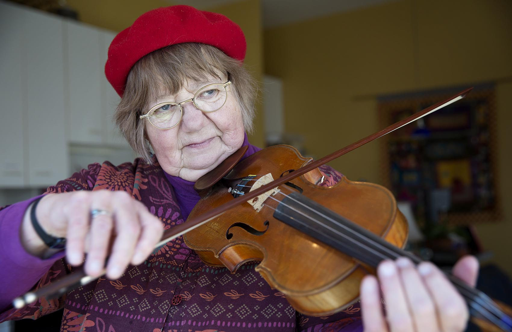 Betty Hauck, a musician suffering from hearing loss, plays her violin at home in Cambridge, Mass. (Robin Lubbock/WBUR)