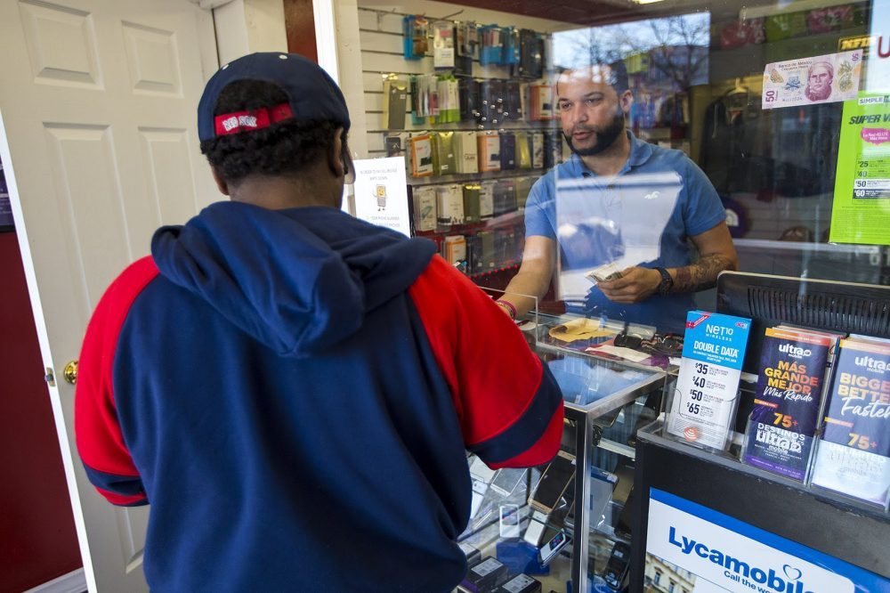 William Sanchez attends to a customer at his shop Bendiciones Wireless in the Bowdoin-Geneva area of Dorchester. (Jesse Costa/WBUR)