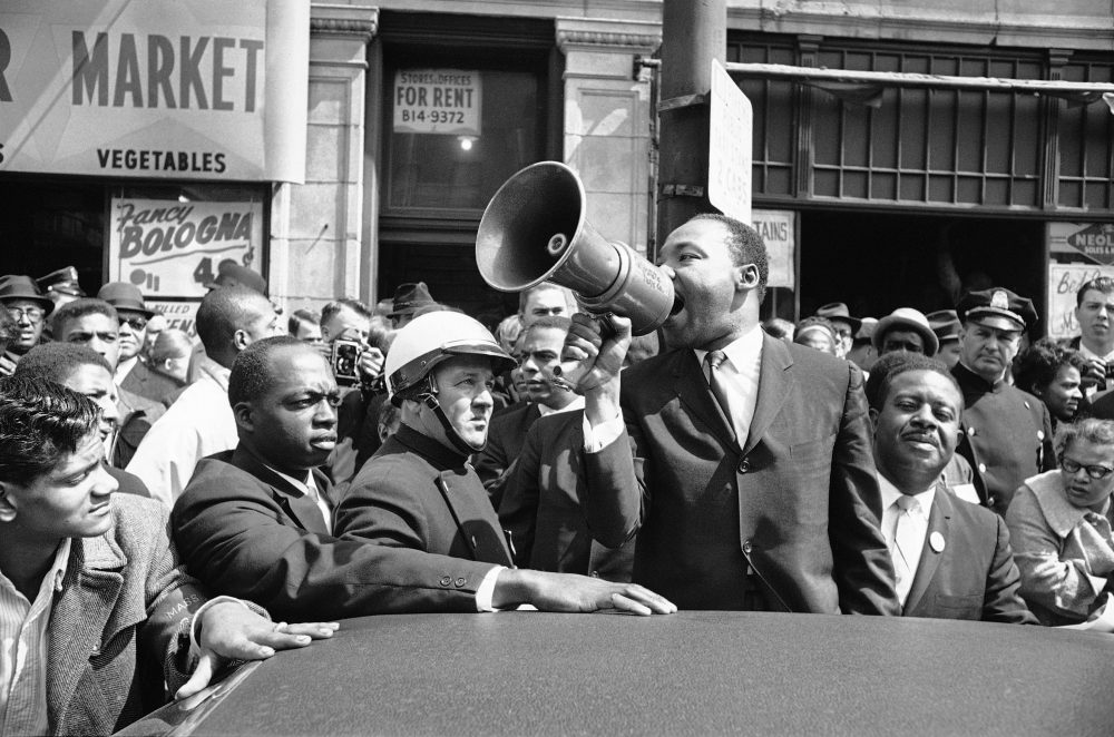 Dr. Martin Luther King Jr., as he addressed a crowd with a bull horn in the Roxbury section of Boston April 22, 1965. King in Boston to lead a civil rights march, made a tour of the Roxbury section to view some of the schools in a predominantly African American  district. He urged spectators to take part in the march. He will address a joint session of the Massachusetts Legislature. (AP Photo)