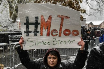 People carry signs addressing the issue of sexual harassment at a #MeToo rally outside of Trump International Hotel on Dec. 9, 2017 in New York City. (Stephanie Keith/Getty Images)