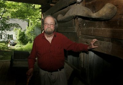 In this June 13, 2006, file photo, Donald Hall, author of numerous poetry books, poses in the barn of the 200-year-old Wilmot farm that has been in his family for four generations. Hall, a prolific, award-winning poet and man of letters widely admired for his sharp humor and painful candor about nature, mortality, baseball and the distant past, died at age 89. (Jim Cole/AP)