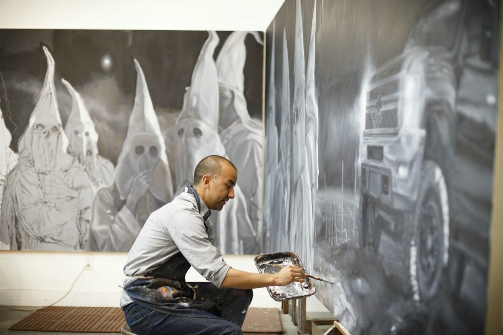 Mexican American artist, Vincent Valdez works on an eight panel painting of modern day klansmen, in his studio in San Antonio, Friday, February 27, 2016. (Photo by Michael Stravato)