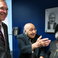 Leo Sarkisian, center, his wife, Mary, and VOA Director David Ensor smile during a celebration that followed the renaming of VOA Studio 23 in Sarkisian's honor, Jan. 29, 2014. (Courtesy VOA)