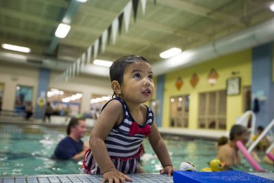 In addition to getting used to being in water and swimming, children also learn how to enter and exit the pool properly. Twenty-two-month-old Charlotte Joshi climbs out of the pool during a toddler swim class at the YMCA in Waltham. (Jesse Costa/WBUR)