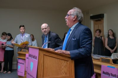 Reps. James O'Day, Paul Brodeur and Jack Lewis address activists. (Chris Triunfo/State House News Service)