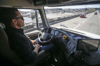 A senior program engineer at Otto, which was acquired by Uber in 2016, takes his hands off the steering wheel of the self-driving, big-rig truck during a highway demonstration. (Tony Avelar/AP)