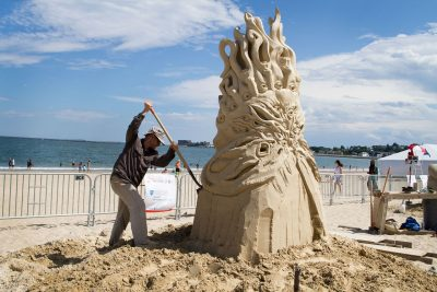 Guy Olivier Deveau from Montreal works on his sculpture at Revere Beach in 2015. (Hadley Green for WBUR)