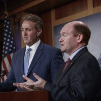 Sen. Jeff Flake, R-Ariz., left, and Sen. Chris Coons, D-Del., talk to reporters after making speeches on the Senate floor calling for a resolution to back the U.S. intelligence community findings that Russia interfered in the 2016 election and calling for other responses to the meddling, on Capitol Hill in Washington, Thursday, July 19, 2018. (J. Scott Applewhite/AP)
