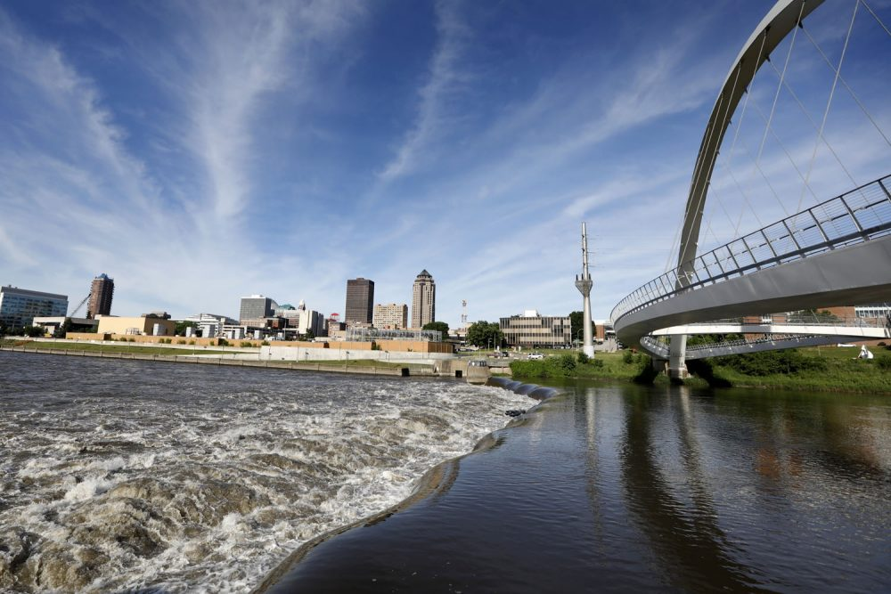 In this Wednesday, June 13, 2018, photo, the Des Moines River water flows over the Center Street Dam, in downtown Des Moines, Iowa. US cities are building whitewater courses and encouraging greater use of urban waterways, but the efforts come as they struggle with pollution in their rivers. In Des Moines, officials support a $117 million plan to attract paddlers to often polluted rivers in the city's downtown and suburbs. (AP Photo/Charlie Neibergall)