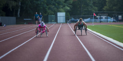 Maddie Wilson, left, and Tatyana McFadden work out together at Wellesley High School, preparing for the upcoming Falmouth Road Race. (Jesse Costa/WBUR)
