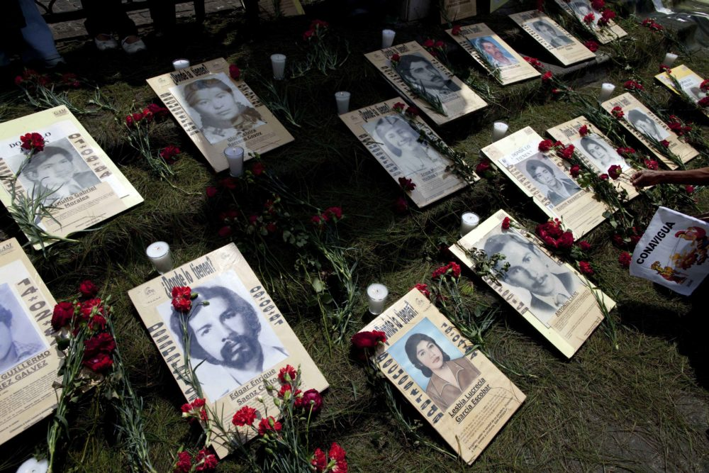 Portraits of people who were allegedly disappeared by the Guatemalan army lay in front of the cathedral during a protest by human rights activists in Guatemala City on Feb. 24, 2011. (Rodrigo Abd/AP)