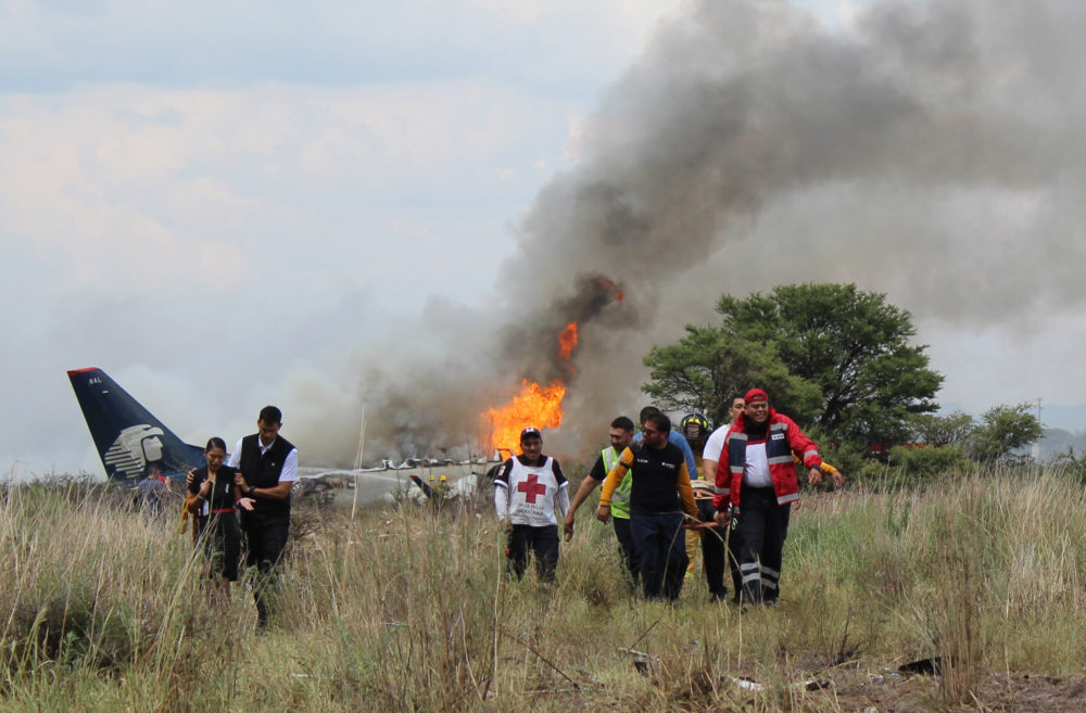 Red Cross and rescue workers carry an injured person on a stretcher, as airline workers walk away from the site where an Aeromexico airliner crashed in a field near the airport in Durango, Mexico July 31, 2018. (Red Cross Durango via AP)