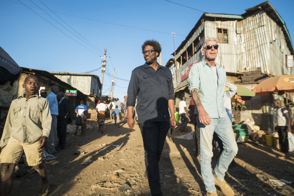 "Anthony Bourdain (right) with W. Kamau Bell in the Kibera slums in Nairobi, Kenya, while filming the first episode of the final season of CNN's ""Parts Unknown."" (Courtesy David Scott Holloway via CNN)"