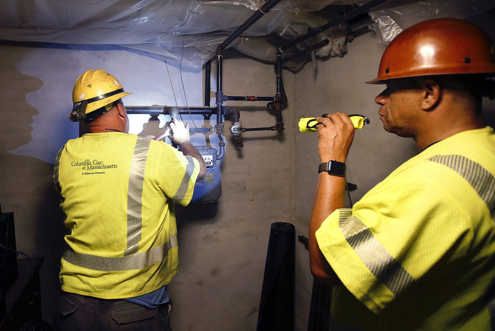 Columbia Gas employee Brian Jones shines a flashlight so his partner, using a wrench, can shut off the gas in a home Friday, Sept. 14, 2018, in Andover, Mass. Multiple houses were damaged Thursday afternoon from gas explosions and fires triggered by a problem with a gas line that feeds homes in several communities north of Boston. (Winslow Townson/AP Photo)