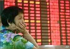 An investor looks at the stock price monitor at a private securities company in Shanghai, China. (AP)
