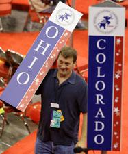 A worker carries the state standard for Ohio on the floor of the Republican National Convention in St. Paul, Minn., Sunday, Aug. 31, 2008. (AP Photo/Charlie Neibergall)