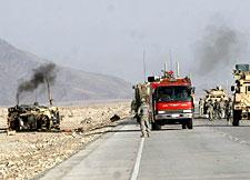 A damaged U.S. vehicle (left) is seen after a suicide attack on a U.S. military convoy in Nangahar province, east of Kabul, on Friday, Oct. 10, 2008. (AP)