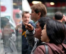 People stop to look through the windows of the Nasdaq MarketSite Tuesday, Oct. 14, 2008, in New York. (AP Photo/Mark Lennihan)