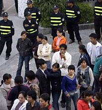 Police stand guard as workers gather in a standoff over a wage dispute at the gate of Jianrong Suitcase Factory in Dongguan, China, on Dec. 19, 2008. (AP)