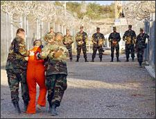 Army Military Police escort a detainee to his cell in Camp X-Ray at Naval Base Guantanamo Bay, Cuba, on Jan. 11, 2002. (AP)