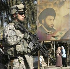 A U.S. Army soldier stands guard next to a poster depicting radical Shiite cleric Muqtada al-Sadr during the reopening of a street in the Kazimiyah area of northern Baghdad, Iraq, on Feb. 3, 2009. (AP)