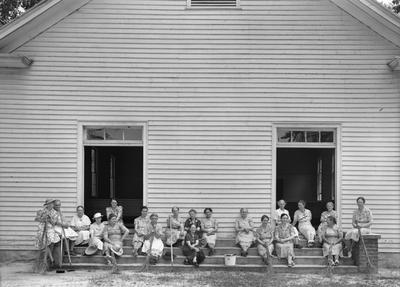 """(Lange) July 5, 1939. Women of the congregation of Wheeley's Church in North Carolina.  This photo inspired Professor Anne Whiston Spirn to delve into the work of Lange. Lange's original caption: """"Women of the congregation on the church steps with brooms and buckets. They have assembled to be photographed."""""""