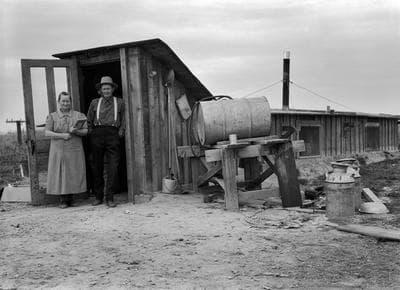 "(Lange) Lange's original caption: ""October 15, 1939. Dead Ox Flat, Malheur County, Oregon. The Wardlaw couple at entrance of basement dugout home."""