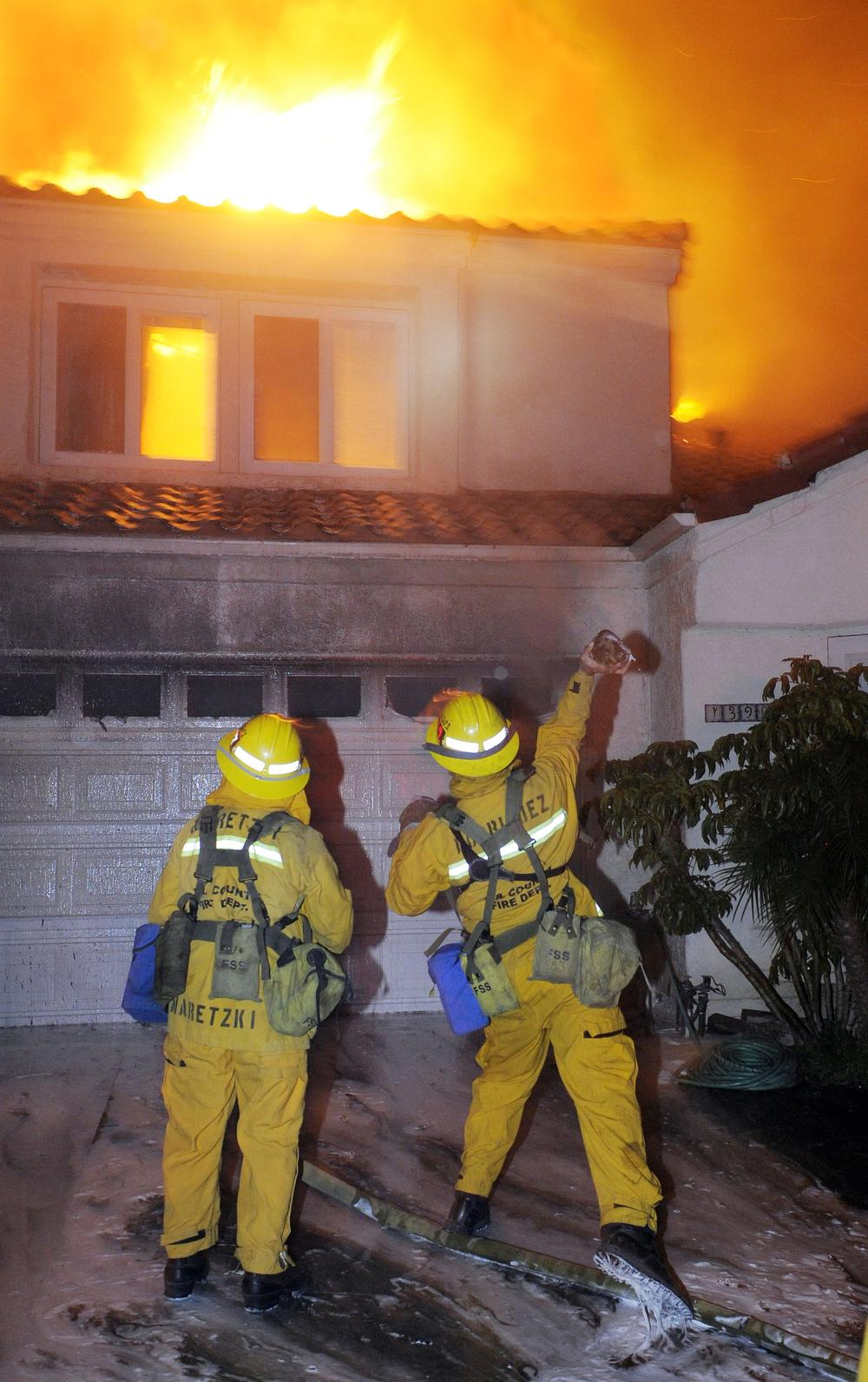 Firefighters throw a rock through a window to spray water inside a home in Los Angeles in 2008.  (AP)