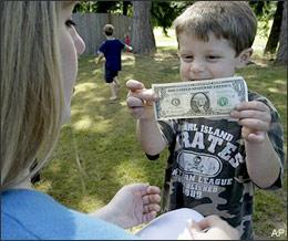 A six-year-old boy proudly displays a dollar that he earned by selling found golf balls back to golfers at the course near his family's home near Seattle, Wash., in July 2008. (AP)