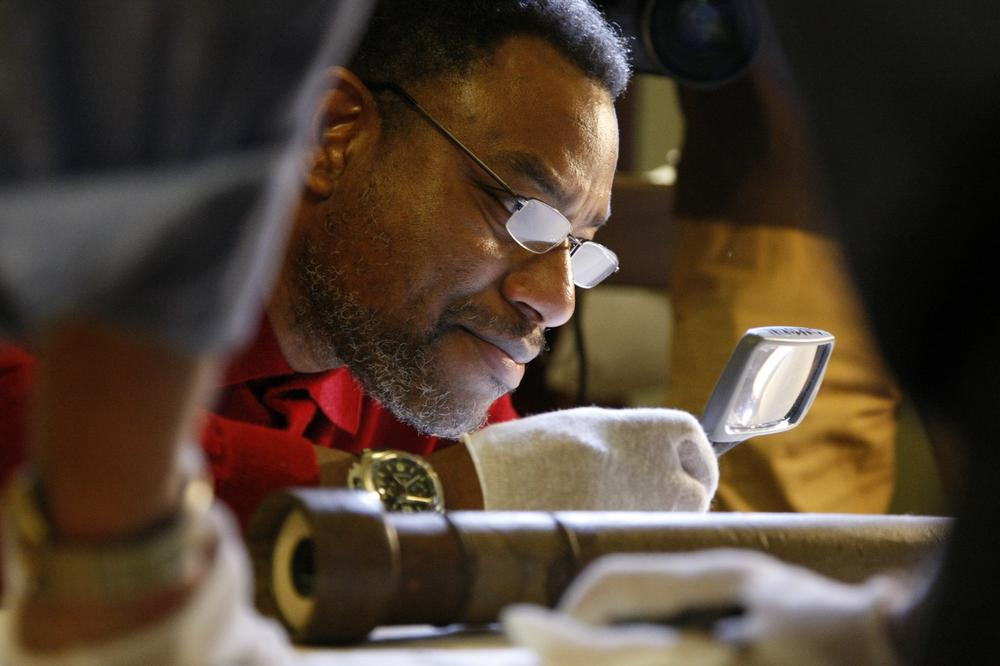 Franklin Chief Astronomer Derrick Pitts examining Galileo's original telescope. (Franklin Institute)