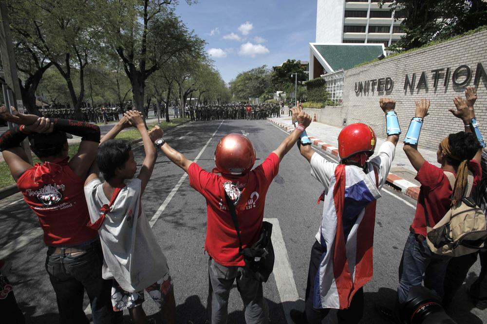 Thai anti-government protesters show surrender gesture against through a line of soldiers outside the government house in Bangkok, Thailand, Tuesday, April 14, 2009. (AP)