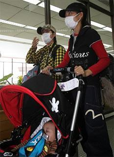 Airline passengers, some wearing face masks, arrive at the Ninoy Aquino International Airport in the Philippines Monday April 27, 2009. (AP)