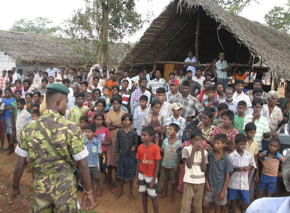 A Sri Lankan police commando stands guard as ethnic Tamils look on during the visit of French Foreign minister Bernard Kouchner, unseen, at the Manik Farm camp for internally displaced ethnic Tamils in Vavuniya, Sri Lanka, Wednesday, April 29, 2009. (AP)
