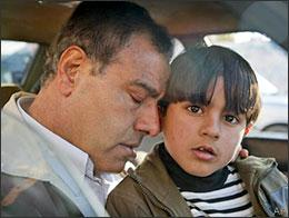 Dr. Ezzeldeen Abu al-Aish rests his head on his son Abdullah, 6, in a car near his house in Jebaliya, in the northern Gaza strip, Jan. 21, 2009. Three of his daughters and a niece were killed by an Israeli shell which struck his house, and he returned to Gaza to collect his remaining children. (AP)