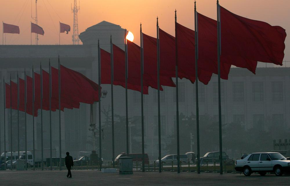 A lone man walks alongside red flags after the clearing Tiananmen square for security reasons ahead of  the opening session of the National People's Congress in  Beijing's Great Hall of the People Sunday, March 5, 2006. (Elizabeth Dalziel/AP)