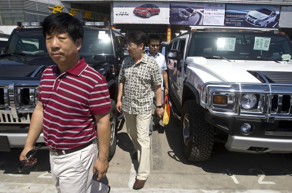 Customers walk between two Hummer vehicles in a parking lot of an auto market in Beijing Wednesday, June 3, 2009.  (AP)
