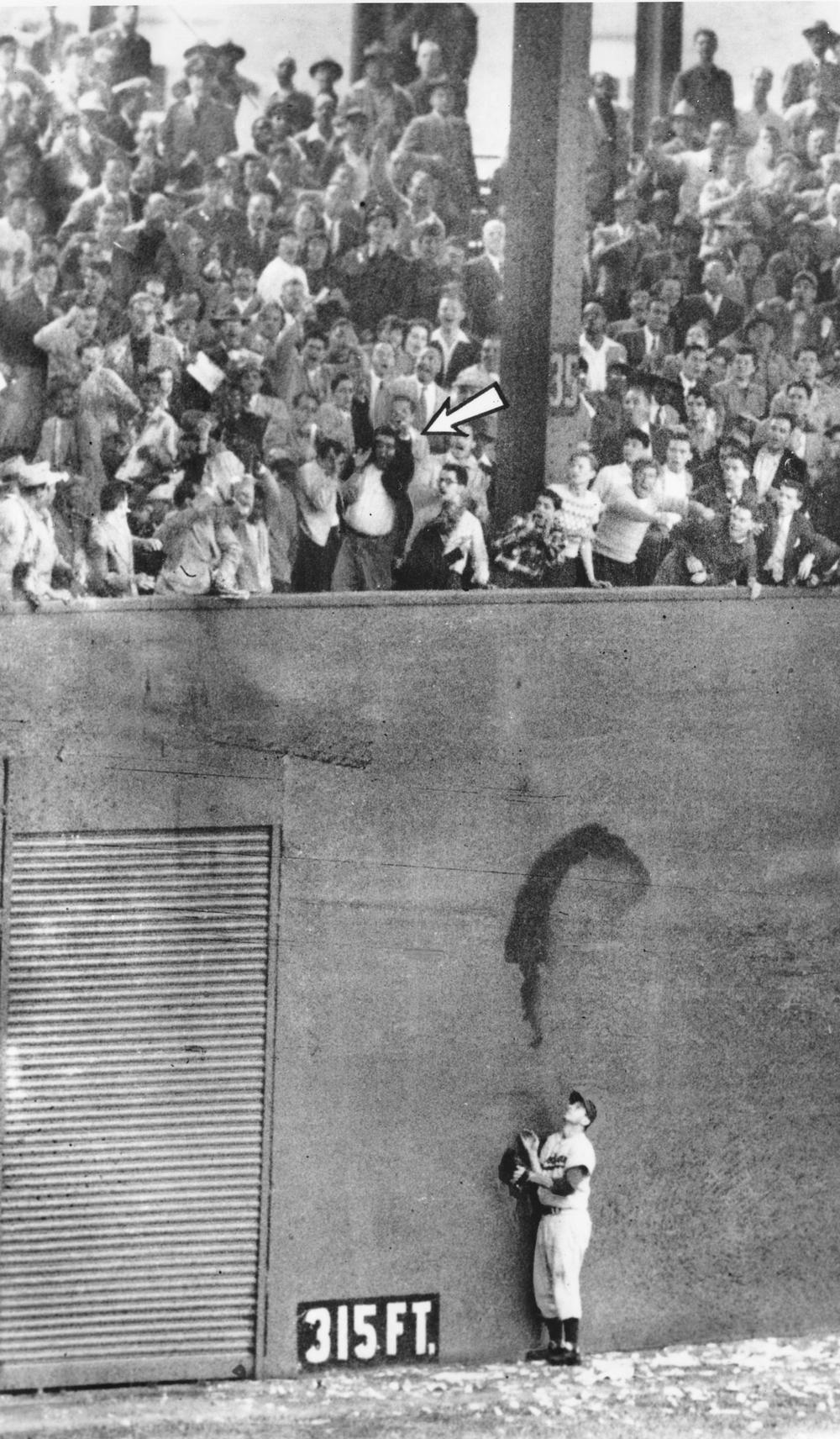 """Brooklyn Dodgers left fielder Andy Pafko watches as """"the miracle ball"""" sails over the wall Oct. 3, 1951. (AP)"""