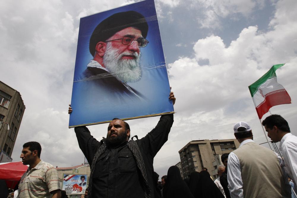 An Iranian man holds a poster of the supreme leader Ayatollah Ali Khamenei after Friday prayers in Tehran, Iran (AP)
