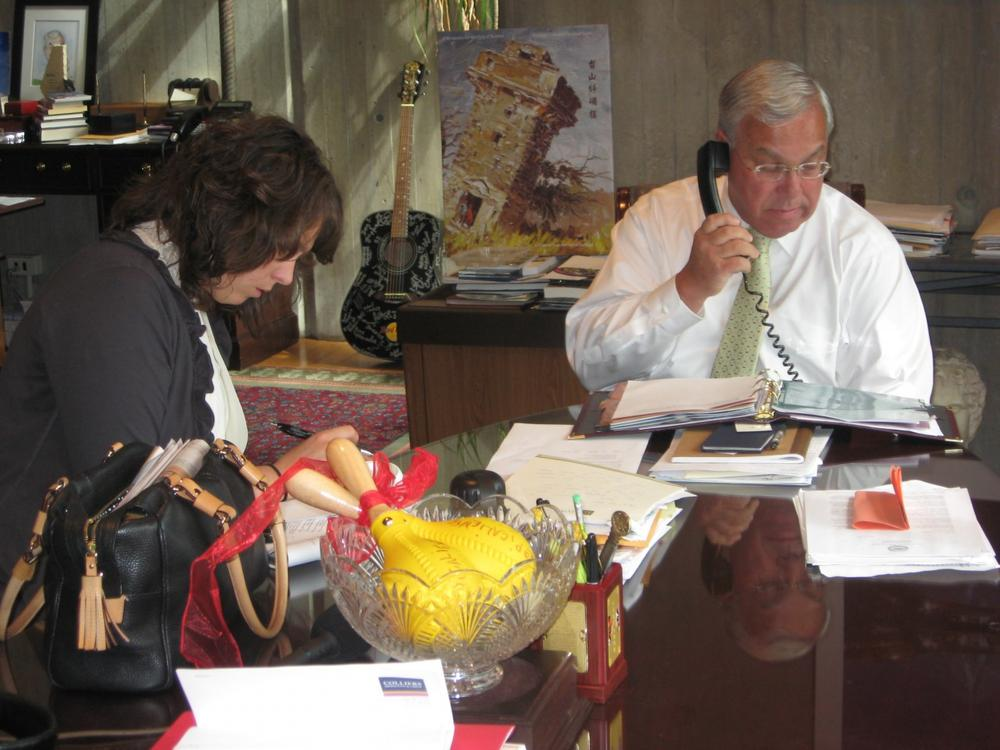 Boston Mayor Thomas Menino conducts a phone interview with a Boston Globe reporter in his City Hall office while press secretary Dot Joyce writes his talking points. (Fred Thys/WBUR)