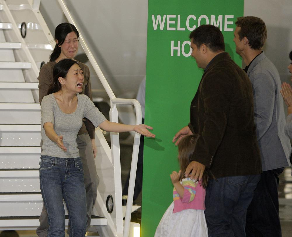 American journalists Euna Lee, left, and Laura Ling, are greeted by Michael Saldate, the husband of Euna Lee, second from right, Ian Clayton, the husband of Laura Ling, right, and Lee's daughter, Hana, after the two arrived at Bob Hope Airport in Burbank, Calif., Wednesday, Aug. 5, 2009. (AP)