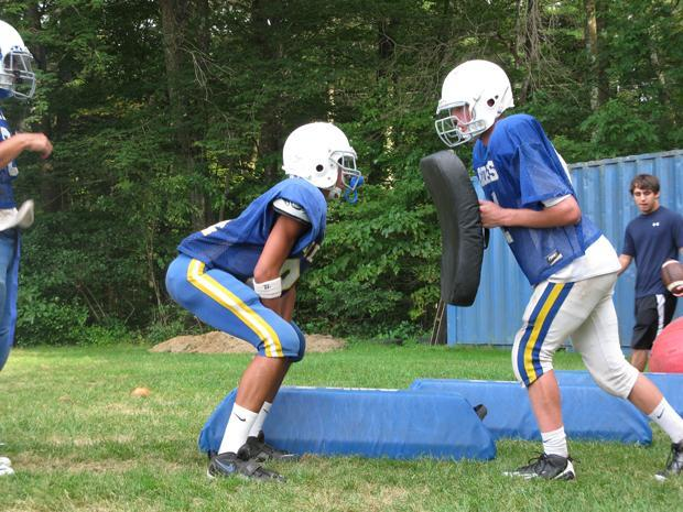 Dover-Sherborn High School football players practice tackling technique in an early season work out. The athletic department launched a computerized concussion management program this fall. (Meghna Chakrabarti/WBUR)