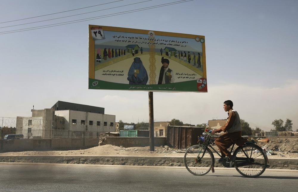An Afghan youth rides his bike, passing by an election billboard that asks the people to vote, in Kabul, Afghanistan on Monday, Oct. 19, 2009.  (AP)
