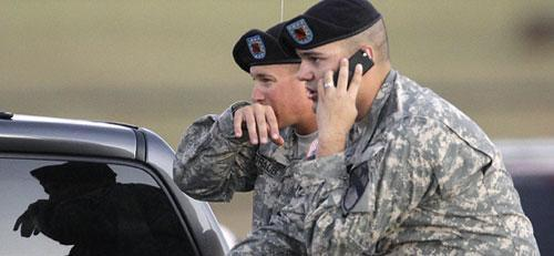 Spc. Ryan Howard of Niles, Mich., right, and Spc. David Straub of Ardmore, Okla., wait for news of fellow soldiers while waiting at the gate of the Fort Hood, Texas, Army base on Thursday, Nov. 5, 2009. (AP)